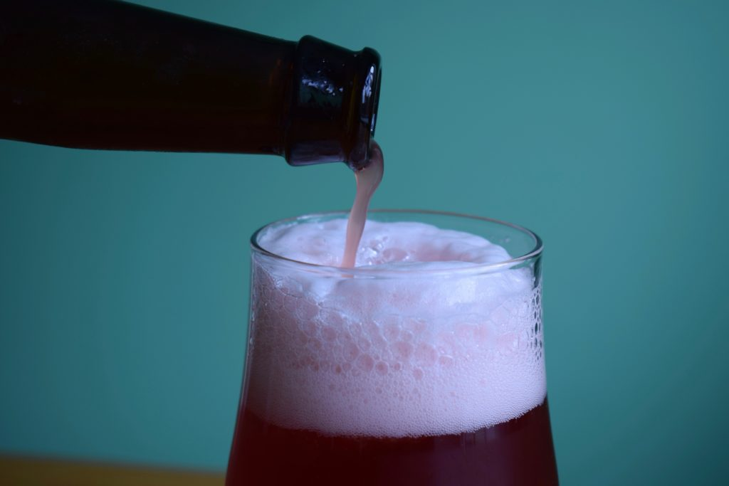 Mikkeller Raspberry Limbo non-alcoholic sour beer being poured into glass