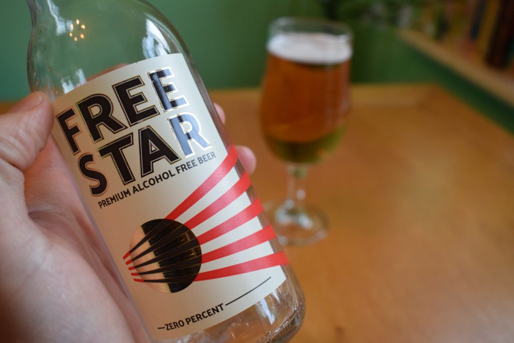Close up of Freestar beer bottle in hand with glass in background
