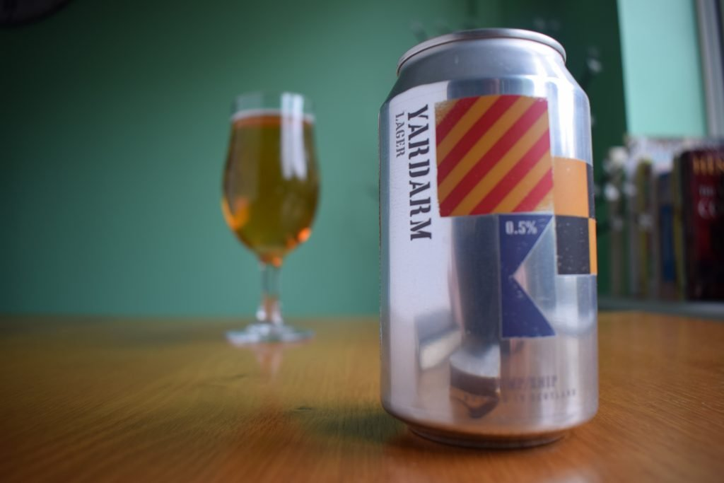 Close up of can of Jump Ship Yardarm non-alcoholic lager with glass in background