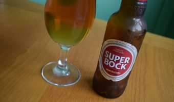 Close up of bottle of Super Bock non-alcoholic label on bottle with glass