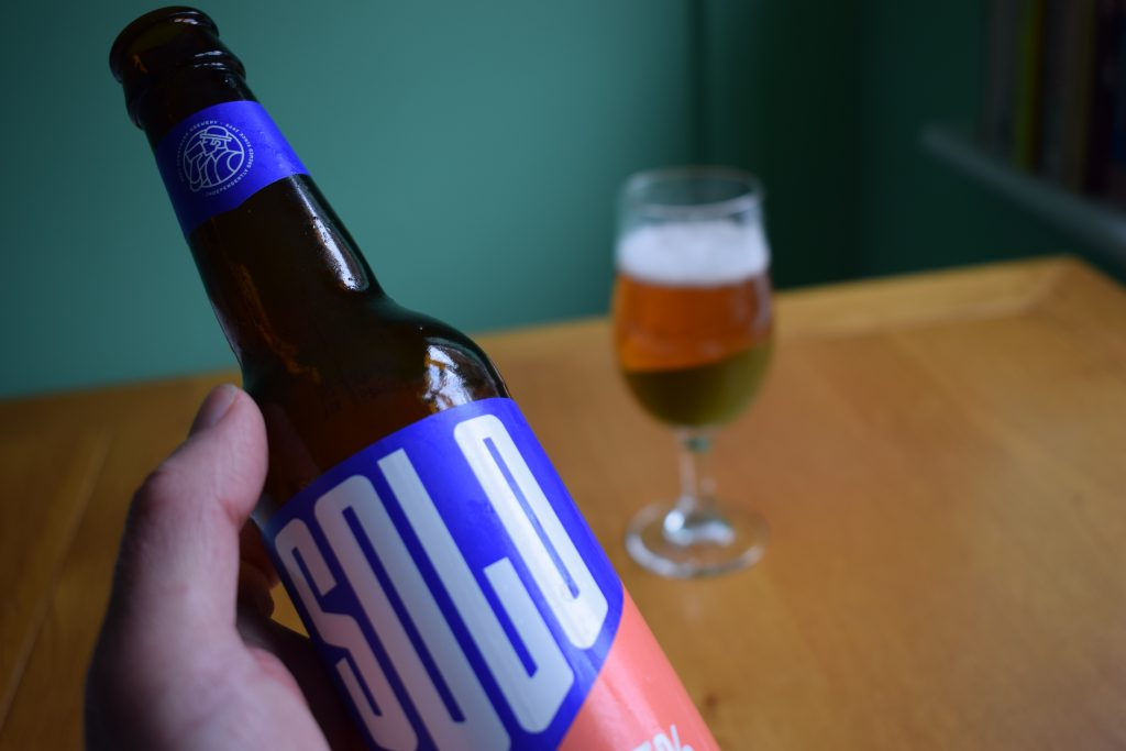 Bottle of WBB Solo non-alcoholic beer with glass on background