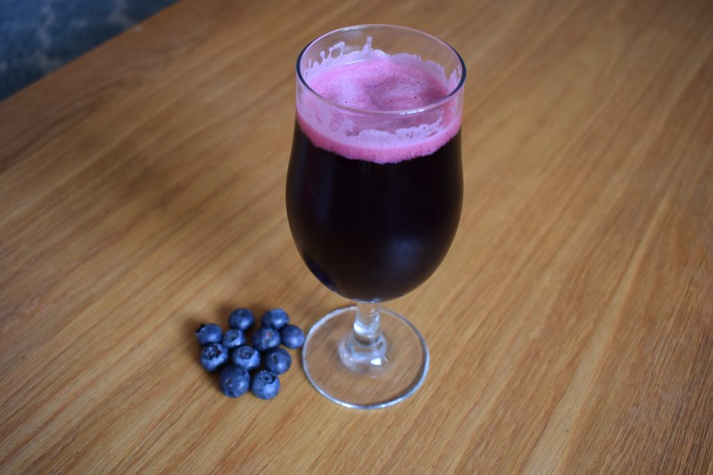 Glass of Mikkeller Limbo blueberry non-alcoholic beer shot from above with pile of fresh blueberries beside it
