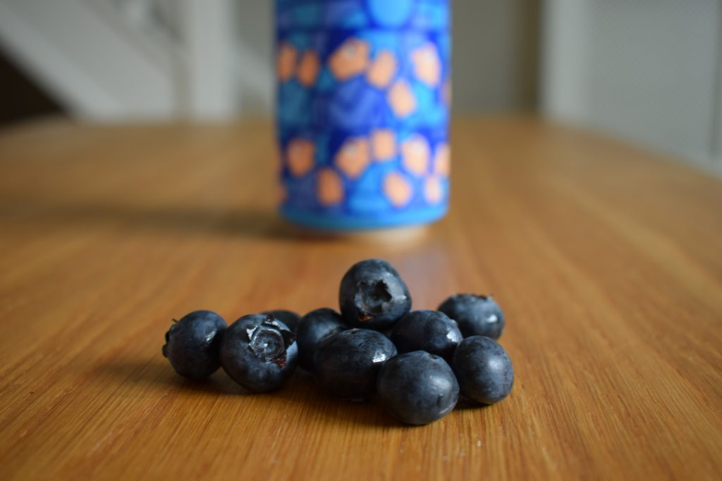 Close up of pile of fresh blueberries with can of Mikkeller Limbo Blueberry non-alcoholic beer in background