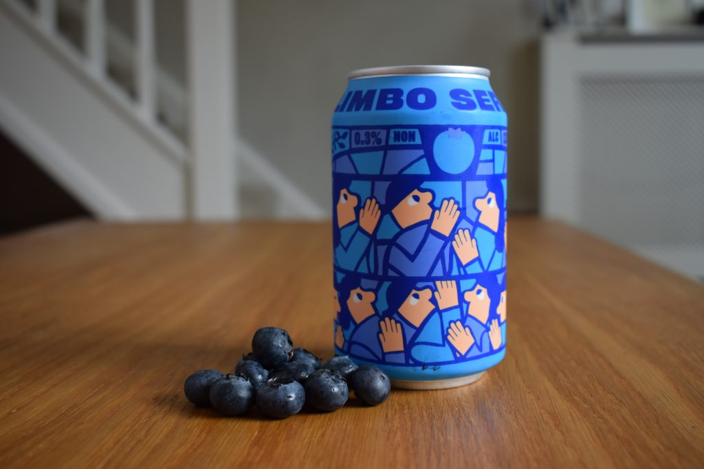 Can of Mikkeller Limbo blueberry non-alcoholic beer shot from above with pile of fresh blueberries beside it