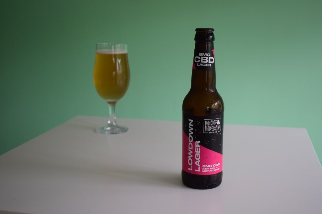 Bottle of Hop and Hemp Lowdown lager with glass in background
