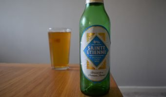Aldi Sainte Etienne Alcohol Free beer bottle with glass in background