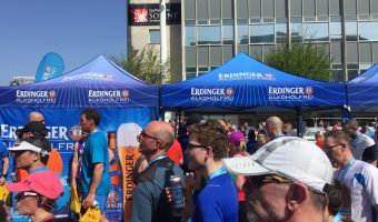 An isotonic non-alcoholic beer stand at the finish of a running race with runners in foreground.