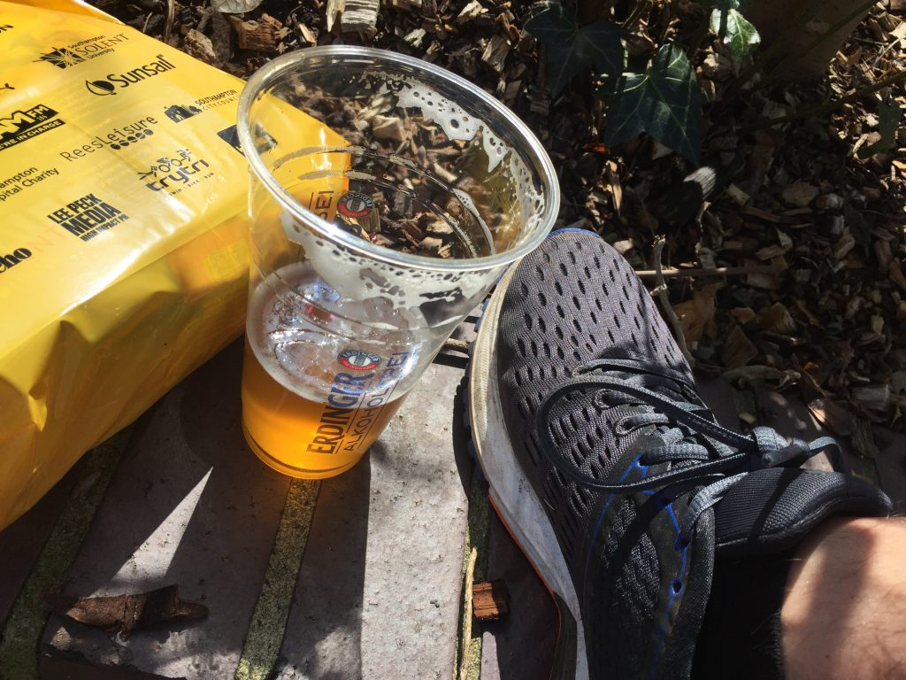 A glass of isotonic non-alcoholic beer next to a running shoe