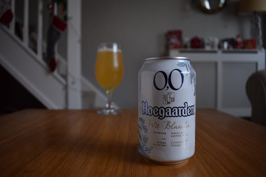 Can of Hoegaarden 0.0 beer with glass in background