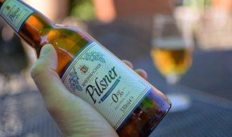 Rheinbacker Pilsner Aldi 0% beer with glass in background