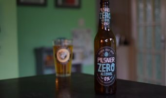 Sainsbury's Pilsner Zero Alcohol bottle with glass in background