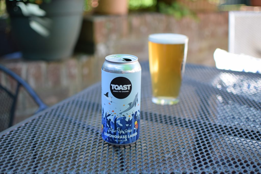 Toast Lemongrass Lager can with glass in background